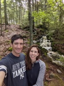Two smiling adults stand in the woods next to a waterfall